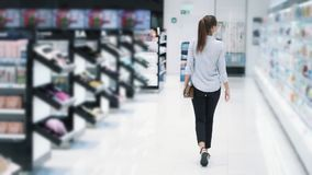 Backside view, girl shopping in cosmetics shop, go between shelves, slow motion. Backside view, girl shopping in cosmetics store, goes between shelves, slow stock video footage