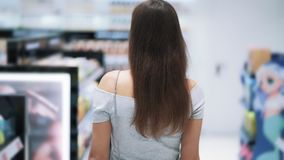 Backside view, girl shopping in cosmetics shop, go between shelves, slow motion. Backside view, girl shopping in cosmetics store, goes between shelves, slow stock video