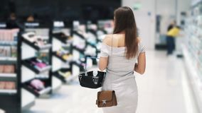 Backside view, girl shopping in cosmetics store with basket, slow motion. Steadicam shot. Concept of purchases, mall stock video footage