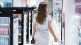 Backside view, girl shopping in cosmetics store with basket, slow motion. Steadicam shot. Concept of purchases, mall stock footage