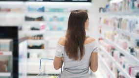 Backside view, girl shopping in cosmetics store with basket, slow motion. Steadicam shot. Concept of purchases, mall stock video