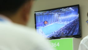 Backside view man looks at large tv screen showing stadium stock video