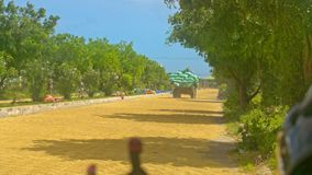 Trailer Vehicle Loaded with Rice Bags Drives along Road. Backside view old trailer vehicle loaded with rice bags drives along sand country road among plants stock video