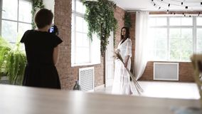 Backside view of a photoshooting process. Beautiful young pregnant photo model in white peignoir posing for female stock video footage