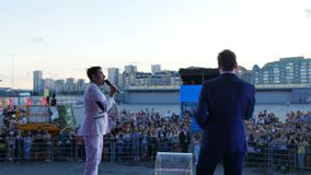 Backside View Presenters Hold Festival Amusing Audience. KAZAN, TATARSTAN/RUSSIA - NOVEMBER 03 2017: Backside view charismatic presenters in white and dark suits stock video footage