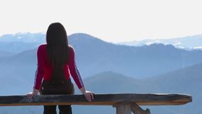 Young woman sits on bench outside and look at pictorial landscape with mountains stock video