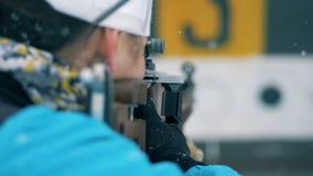 Backside view of a sportswoman shooting on a biathlon stadium. 4K stock video