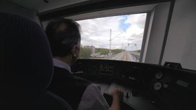 Machinist drives train along railway on sunny day. Backside view from train cabin engine driver drives modern powerful train along railway on sunny day past stock video footage