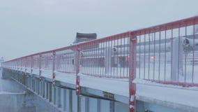 Backside View Truck Drives on Bridge against Cloudy Sky. SALEHARD, YAMAL-NENETS/RUSSIA - JANUARY 14 2013: Backside view truck drives on bridge with red handrails stock video footage