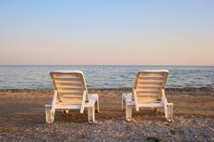 Backside view two beach chairs in the evening. Beach chaise longues beside tranquil sea on the morning. Clear sky Stock Images