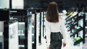 Backside view, woman goes on cosmetics store between shelves, slow motion. Steadicam shot. Concept of purchases, mall stock video