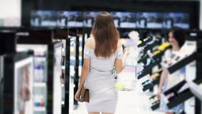 Backside view, woman goes among shelves in cosmetics shop, slow motion. Backside view, young woman with basket goes among shelves in cosmetics shop, slow motion stock video footage