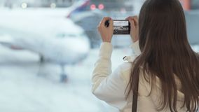 Backside view woman takes photo of airplane near window at airport. Female tourist in white jacket uses smartphone in terminal hall. Concept travel, journey stock video