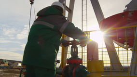 Backside View Worker Turns Level at Oil Extracting Well. KAZAN/TATARSTAN/RUSSIA - NOVEMBER 15 2016: Backside view motion to worker in uniform jacket turning stock video footage