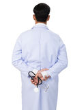 Backside view of young doctor, physician holding his stethoscope. Backside view of doctor, physician with a stethoscope in the hands at workplace - health care royalty free stock image