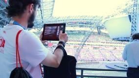 Backside View Young Man with Beard Shoots Modern Arena. KAZAN, TATARSTAN/RUSSIA - MAY 15 2013: Backside view young man with beard shoots on tablet modern sports stock footage