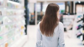 Backside view, woman goes among shelves in cosmetics shop, slow motion. Backside view, young woman with basket goes among shelves in cosmetics shop, slow motion stock video