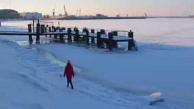 Young woman in long red jacket walking on snow-covered Bank of frozen river near pier, on background of river port. Backside view young woman in long red jacket stock footage