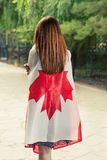 Backside view of young women wrapped around with Canada nation flag Stock Image