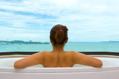 Backside woman in bathtub on sea view Royalty Free Stock Images