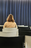 Backside of woman sitting in a theatre. Woman sitting alone in a theatre seat. The curtains are closed Stock Image