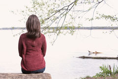 Backside of woman sitting on tree in front of a lake Royalty Free Stock Image