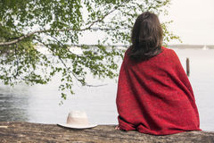 Backside of woman sitting on tree in front of a lake Stock Photos