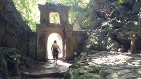 Backside women leave cave through gate in stone arch. DANANG/VIETNAM - MAY 05 2018: Backside view women tourists in straw hats leave cave through gate in stone stock footage
