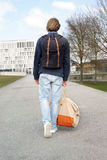 Backside of young man walking in street with bags. Backside of young man with red hair walking in the street with his bags Stock Photos