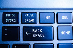 Backspace button on the keyboard closeup. Surrounded with Print Screen, Pause Breack, Insert , Home and other buttons in blue color cast stock photos