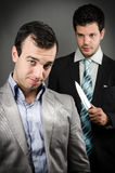 Backstabbing. One worker about to backstab another Royalty Free Stock Image