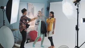 Backstage of the photo shoot: photographer with assistant choosing clothes for model`s photo shooting