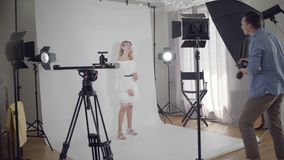 Backstage of the photo shoot. Photographer shakes hands with a model girl standing on white background in the studio. Before shooting. Fashion magazine studio stock video