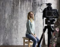 Backstage with professional shooting in the studio. The model sits on a chair with close eyes, a professional camera in the defocus stock images