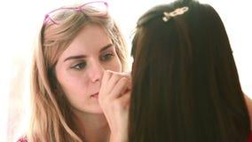 Backstage scene: Professional Make-up artist doing glamour model makeup at work stock video
