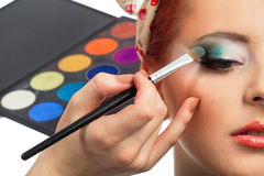 Pinup makeup. Backstage scene: Professional Make-up artist doing pinup model makeup at work royalty free stock images