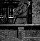 Backsteinbau-großer Zaun und Weiß Windows im Schatten mit Sun Lizenzfreies Stockbild