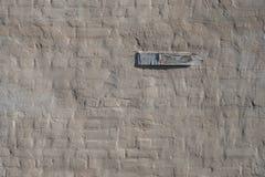 Backsteinmauer bedeckt mit Kitt, hölzerne Plakette auf der Wand Stockfotos
