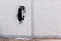 Backsteinmauer, die mit einem großen Loch in ihm demoliert wird Lizenzfreies Stockbild