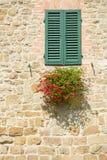 Backsteinmauer, Fenster mit hölzernen Vorhängen und Blume Lizenzfreies Stockfoto