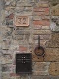 Backsteinmauer mit Adresse und Nummernschildern Stockfoto