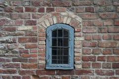 Backsteinmauer mit altem Fenster Stockfotos