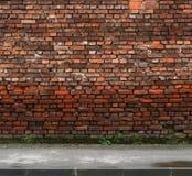 Backsteinmauer mit Bürgersteig Stockbilder