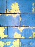 Backsteinmauer mit blauer und gelber Farbe stockbilder