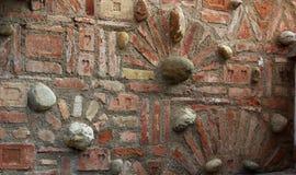 Backsteinmauer mit dekorativen Ziegelsteinen und Steinen Stockbild