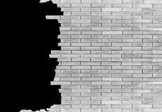 Backsteinmauer mit dem Loch lokalisiert auf schwarzem Hintergrund Lizenzfreie Stockbilder