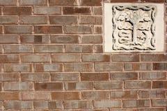 Backsteinmauer mit dem Steinschnitzen Lizenzfreie Stockfotografie