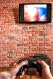 Backsteinmauer mit einem Fernsehen und eine Fernbedienung von der Spielkonsole in der Hand Fokus auf der Wand mit Fernsehen stockbild