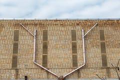 Backsteinmauer mit einem Funkenüberschlagsrohr benutzt für Belüftung stockbilder