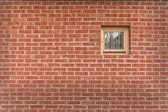 Backsteinmauer mit einem kleinen Fenster Stockfotos